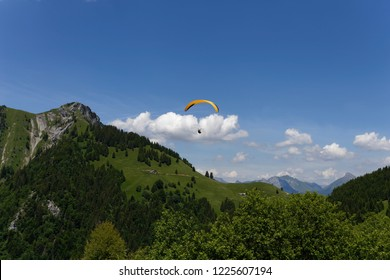 Yellow paragliderflying in blue skies and mountains above Lake  Annecy  France