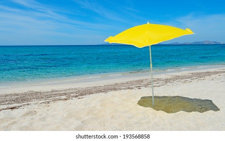 yellow parasol in a desert beach