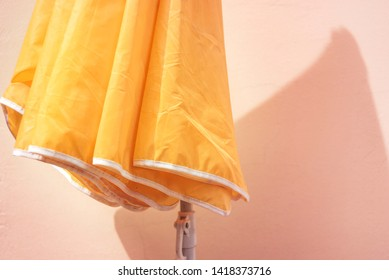 Yellow parasol on a pink wall