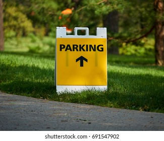 Yellow parking sign with arrow on grass
