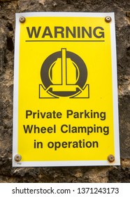 A yellow parking sign warning drivers that car clamping is in operation.