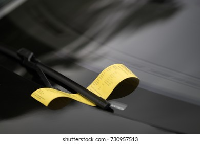 A yellow parking ticket is affixed under the windshield wiper of a black car.