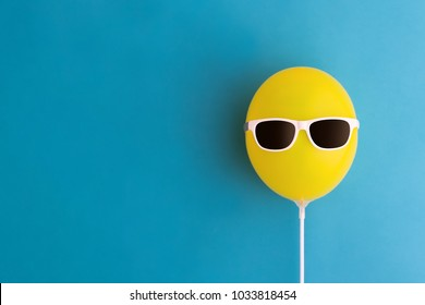 Yellow party balloon with sunglasses on a blue background