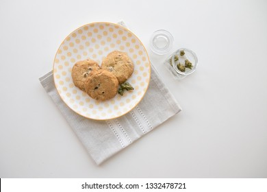 Yellow Patterned Plate with Chocolate Chip Cookies and a Glass Jar with Marijuana Buds