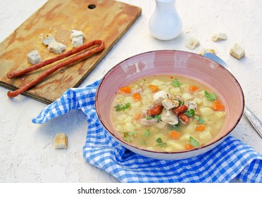 Yellow pea soup with potatoes, carrots, ham and smoked sausages in a clay bowl on a light concrete background. Served with white bread croutons.  Selective focus