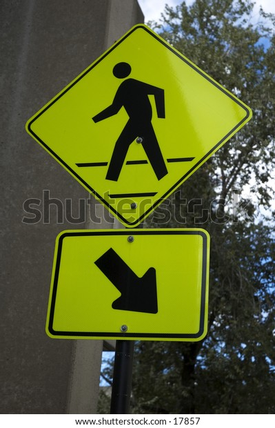 A yellow pedestrian crossing sign