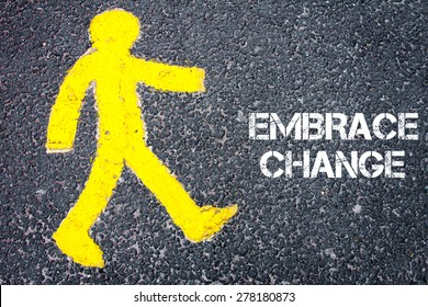 Yellow pedestrian figure on the road walking towards EMBRACE CHANGE. Conceptual image with Text message over asphalt background.