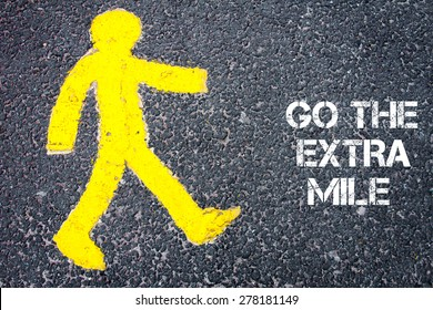 Yellow pedestrian figure on the road walking towards GO THE EXTRA MILE. Conceptual image with Text message over asphalt background.