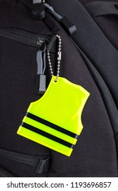 Yellow pedestrian safety reflector on a black backpack, closeup view. Concept of safety
