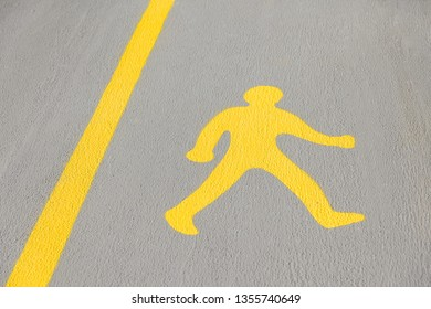 A yellow pedestrian walk sign painted on a concrete walkway.