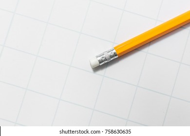Yellow pencil with eraser lies on the paper in the cage for school.
