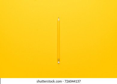 yellow pencil with eraser on paper background