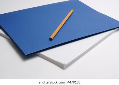 Yellow pencil sitting on top of blue report cover and lined paper for office or business supplies, or for back to school time.