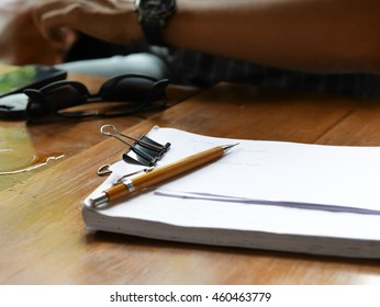 Yellow pencil and white paper on wood background wallpaper