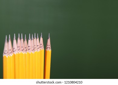 Yellow pencils in line showing a smiling face, and the last one a sad face.