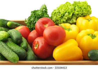 Yellow pepper, tomatoes, cucumbers, lettuce and parsley in wooden tray.