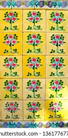 Yellow peranakan tiles with a red and green geometric tree design. Typical of the tiled mosaics which are seen on the facade of traditional peranakan style Chinese shop houses.