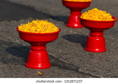 yellow petals of marigolds in the red wooden pedestal trays are on the asphalt road used in thai dance show or buddhist use for respect to the buddha image