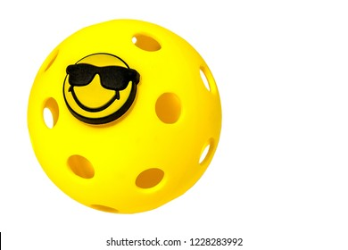 Yellow Pickleball with smiley face attached on a white background.