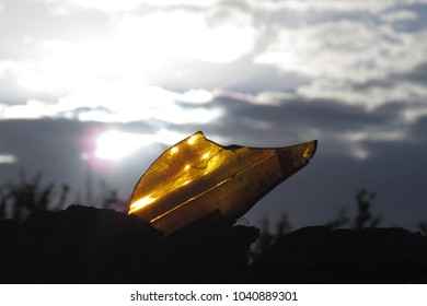 Yellow piece of broken glass on a wall with a sunlight sky background