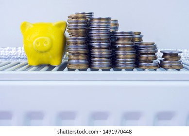 Yellow piggy bank on a home heating radiator. Symbolic image of the high cost of heating, saving money, saving energy, energy efficiency.