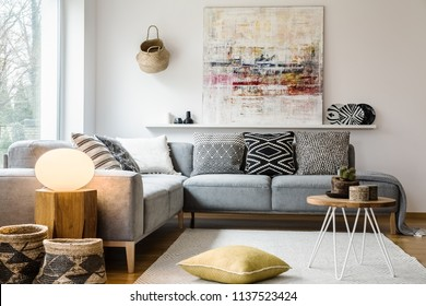 Yellow pillow and table on carpet in bright living room interior with light next to couch. Real photo