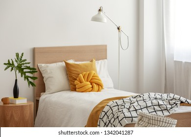 Yellow pillows and cozy blanket on single bed in elegant hotel room,green leaf in black vase on wooden bedside table