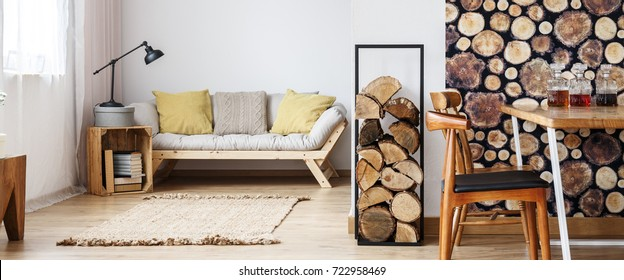 Yellow pillows on beige sofa and lamp on crate in warm autumn room with firewood and wooden furniture