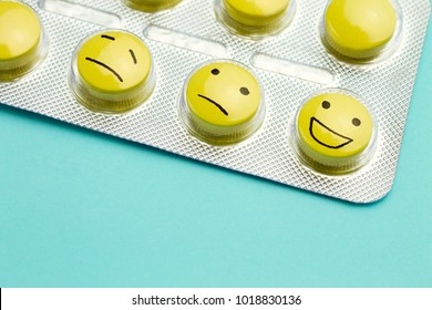 Yellow pills andfunny faces in a blister on a blue background. The concept of antidepressants and healing