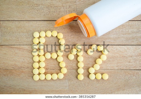 Yellow pills forming shape to B12 alphabet on wood background