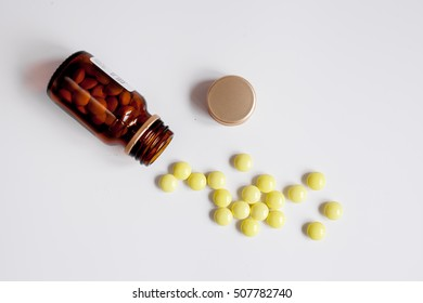 yellow pills in glass bottle on white background