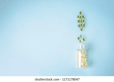 Yellow pills in a jar scattered in the shape of a exclamation mark on a blue background with copy space