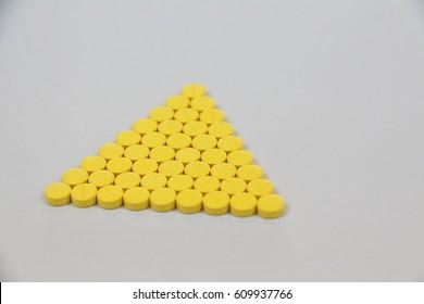 Yellow pills on white background.