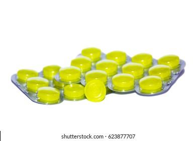 Yellow pills on white background