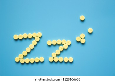 Yellow pills in Z shape. Sleeping pills on blue background
