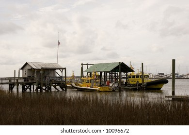 Yellow pilot boats tied up at a pier beyond the marshy wetlands