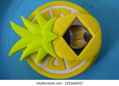 Yellow pineapple-shaped bottle opener and lemon-shaped coasters on a bright blue metal tray.
