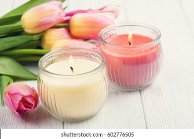 Yellow and pink aroma candles with tulips. SPA composition. Toned vintage