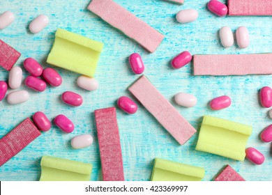 yellow and pink chewing gum with small candies on a blue wooden background