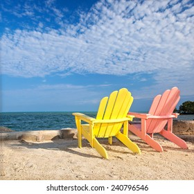 Yellow and pink colorful  lounge chairs on a beach in Florida Keys with blue sky on a sunny summer day