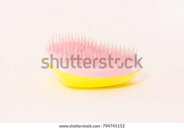 The yellow and pink compact hairbrush on the white background.