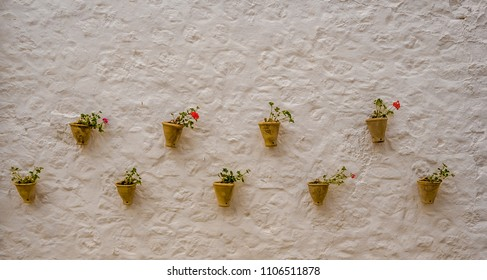 Yellow planters with geraniums on a white wall, typical Andalusian. Spain