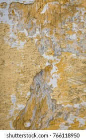 A yellow plaster wall decaying.