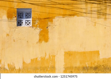 Yellow plastered wall, wrought iron window and shadows of electricity cables, old quarter of Hoi An, Vietnam