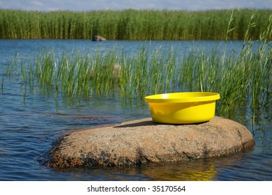 yellow plastic basin on stone by sea