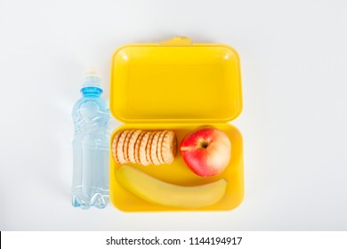 The yellow plastic box with lunch and bottle with water for school lie on a white table.  In the box are a banana, apple and a biscuit,