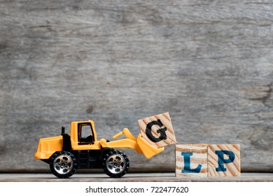 Yellow plastic bulldozer hold letter G to complete word GLP (Abbreviation Good Laboratory Practice) on wood background