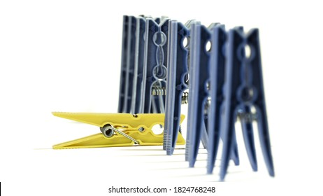 Yellow plastic clothes peg standing out in a group of blue clothes pegs lined up on a white background. Differences, solitude, isolation, creativity, discipline concept