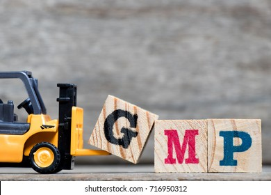 Yellow plastic forklift hold letter G to complete word GMP (Abbreviation of Good Manufacturinc Practice) on wood background