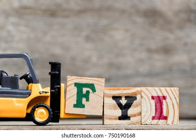 Yellow plastic forklift hold letter F to complete word FYI (Abbreviation of For your information) on wood background